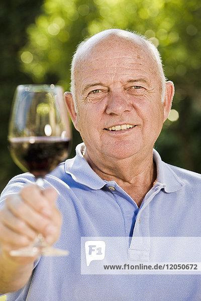 Portrait of Man Raising Glass of Red Wine