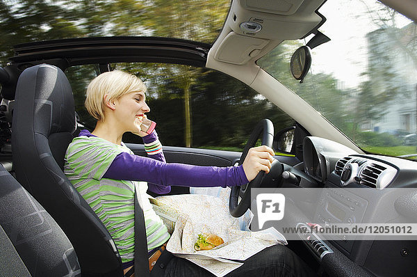 Woman Talking on Cell Phone and Eating While Driving