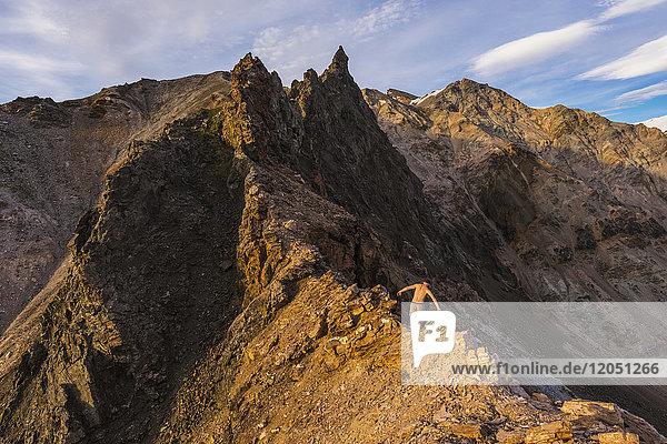 A shirtless hiker scrambles over a craggy ridge in the eastern Alaska Range near Whistler Creek in summer; Alaska  United States of America