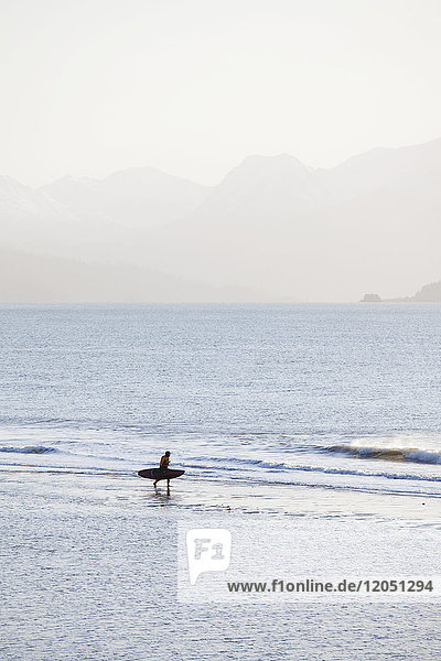 Surfer Walking On Beach  Kachemak Bay With Kenai Mountains In The Background  Homer Spit  Southcentral Alaska  USA