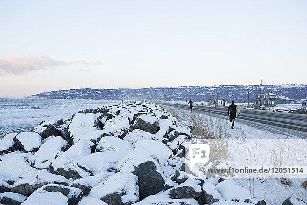 Surfers Walking Along Homer Spit In Winter  Kenai Peninsula  Southcentral Alaska  USA