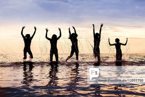 Silhouette of five children jumping out of the water in a row at sunset Sandbanks Provincial Park; Picton  Ontario  Canada