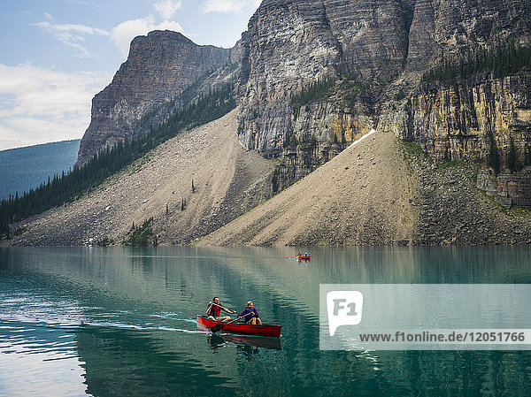 A red canoe in Moraine Lake with a cliff of the Canadian Rocky Mountains along the shoreline; Lake Louise  Alberta  Canada