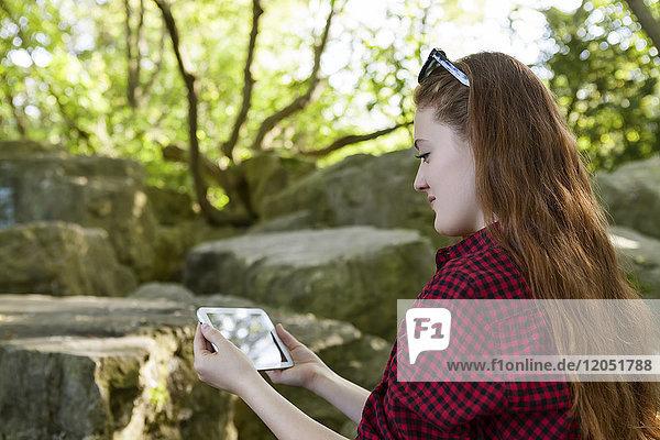 Teenage girl using her smart phone  Woodbine Beach; Toronto  Ontario  Canada