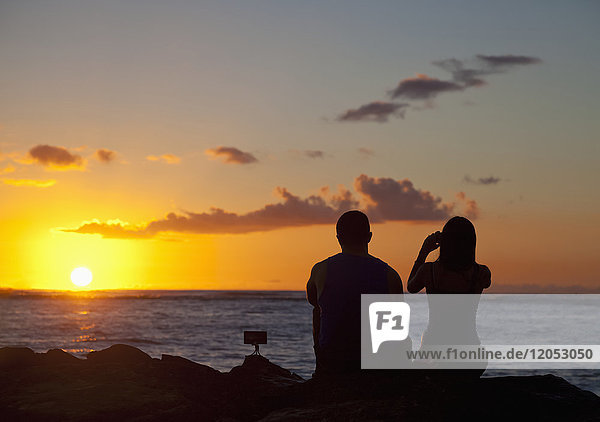 Silhouette of a couple taking pictures and watching the sunset on the beach  Waikiki; Honolulu  Oahu  Hawaii  United States of America