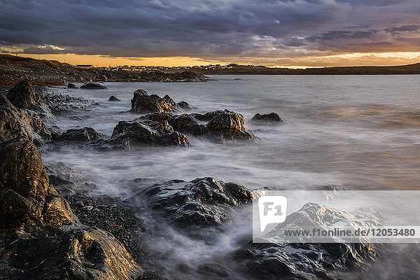 The rugged Atlantic coastline at sunrise under a cloudy sky; Bonavista,  Newfoundland,  Canada