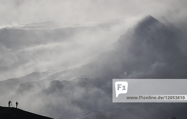 Photographers Silhouetted Against The Snow Laden Mountain; Iceland
