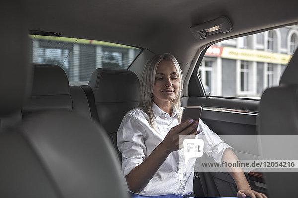 Lächelnde Geschäftsfrau beim Telefonieren im Auto