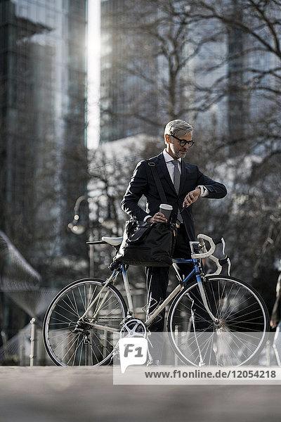 Grauhaariger Geschäftsmann mit Fahrrad und Kaffee zum Mitnehmen in der Stadt mit Blick auf smartwatch