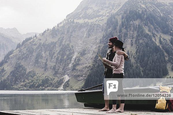 Österreich  Tirol  Alpen  Paar mit Karte am Steg am Bergsee