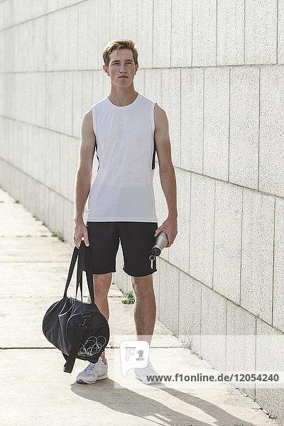 Junger Sportler mit Sporttasche und Trinkflasche im Freien