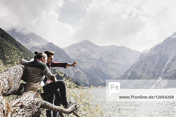 Austria  Tyrol  Alps  couple sitting on tree trunk at mountain lake taking selfie