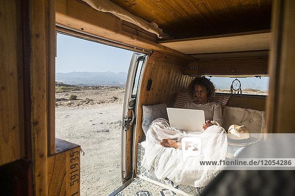 Spanien  Teneriffa  Frau iusing laptop in van