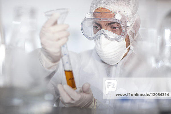 Scientist working in lab holding a cylinder