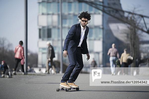 Businessman riding longboard in front of skyscraper