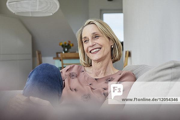 Lächelnde reife Frau zu Hause auf dem Sofa