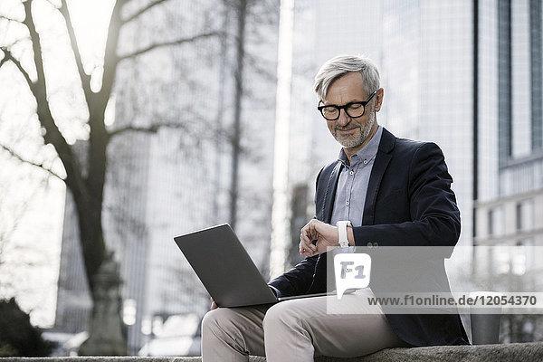 Grauhaariger Geschäftsmann arbeitet mit Laptop an der Wand in der Stadt und schaut auf seine Smartwatch.