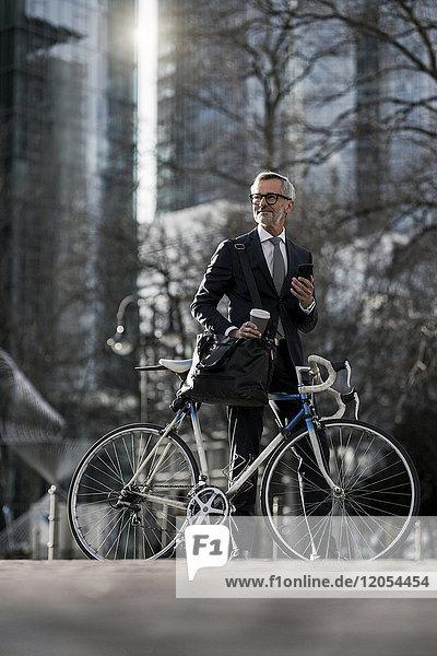 Grauhaariger Geschäftsmann mit Fahrrad und Kaffee zum Mitnehmen in der Stadt