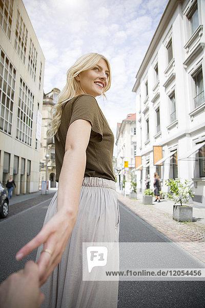 Lächelnde blonde Frau hält Hände auf der Straße