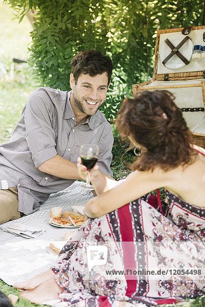 Pärchen bei einem Picknick in einem Park mit Rotwein