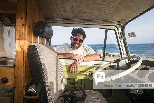 Spanien  Teneriffa  Porträt eines lachenden Mannes  der sich auf das Autofenster lehnt und nach innen schaut.