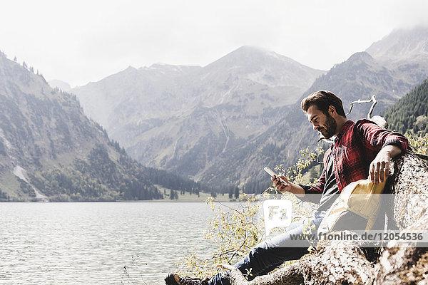 Österreich  Tirol  Alpen  Wanderer entspannt auf Baumstamm am Bergsee beim Handy checken