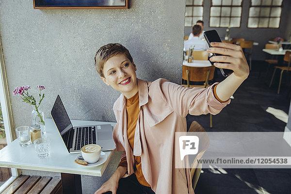 Frau  die einen Selfie mit Kaffee und Laptop im Café nimmt
