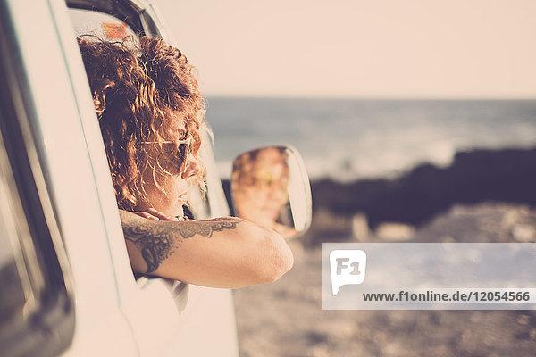 Tätowierte Frau mit Blick aus dem Auto