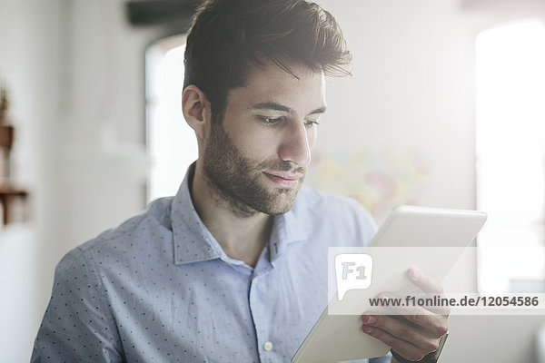 Young businessman working in office  looking at digital tablet