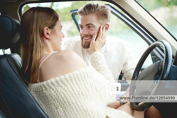 Liebevolles junges Paar im Auto