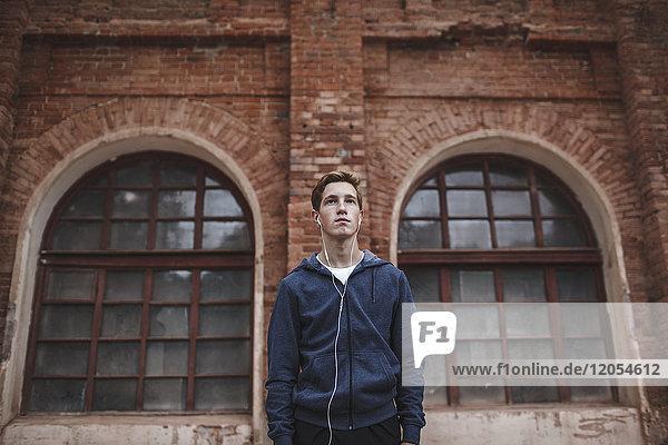Junger Mann mit Kopfhörern am Backsteingebäude stehend