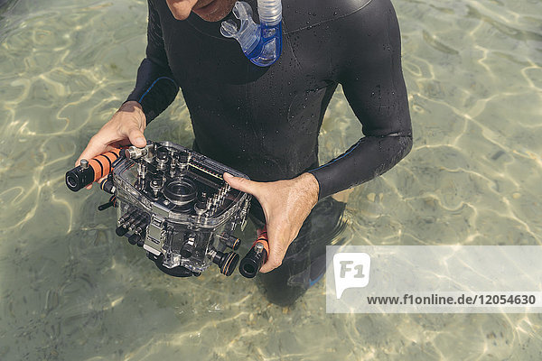 Man holding underwater DSLR camera case in a lake