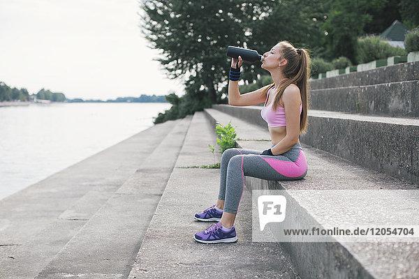 Sportliche Frau trinkt Wasser am Flussufer