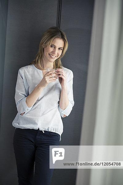 Lächelnde Frau hält ein Glas Wasser am Fenster.