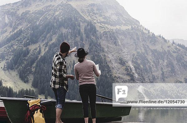 Österreich  Tirol  Alpen  Paar mit Karte am Bergsee stehend