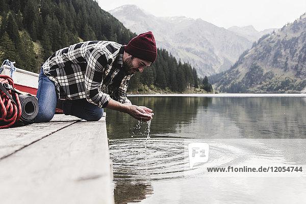 Österreich  Tirol  Alpen  Mann kniend auf dem Steg Wasser aus dem Bergsee schöpfend