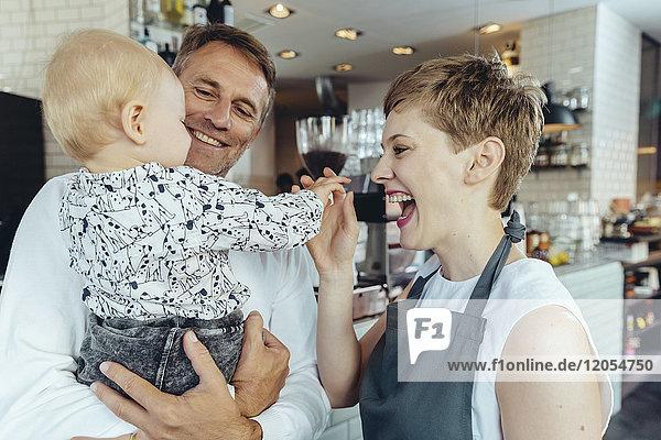 Kellnerin spielt mit Baby des Kunden im Cafe