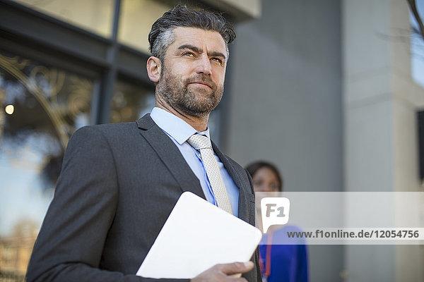 Geschäftsmann im Anzug wartet vor dem Bürogebäude