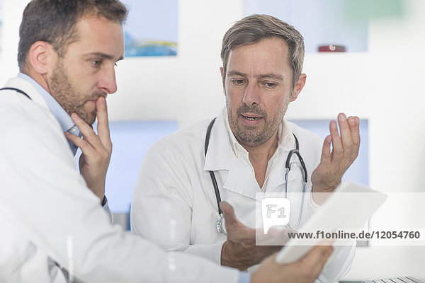 Two doctors with tablet discussing