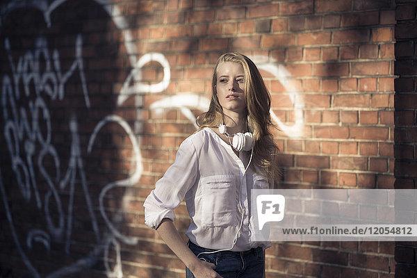 Portrait einer jungen Frau mit Kopfhörer vor der Ziegelwand