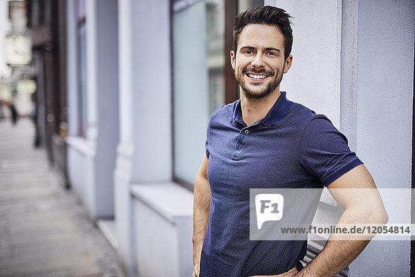 Lächelnder Mann steht auf der Stadtstraße