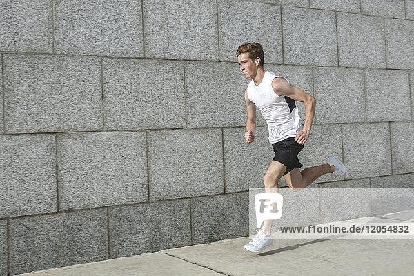 Junger Mann läuft an der Wand entlang