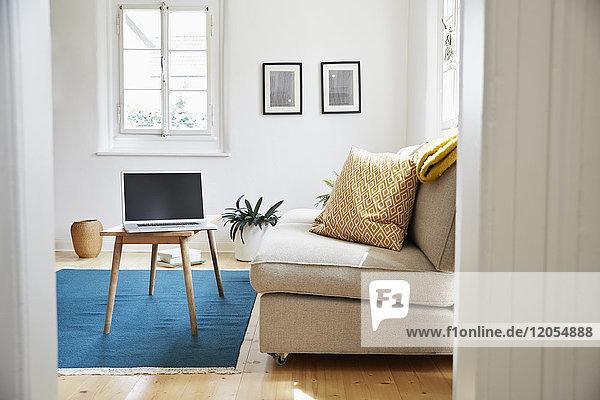 Laptop auf Couchtisch in einem hellen  modernen Wohnzimmer in einem alten Landhaus