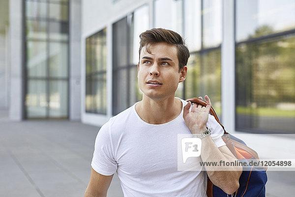 Portrait eines jungen Mannes mit Sporttasche