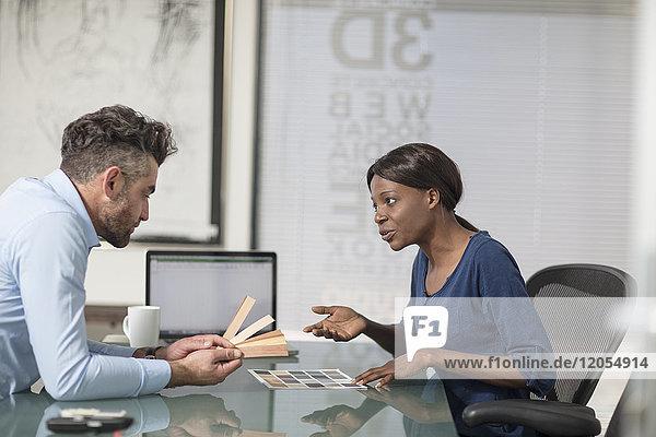 Kollegen diskutieren Farbmuster im Büro
