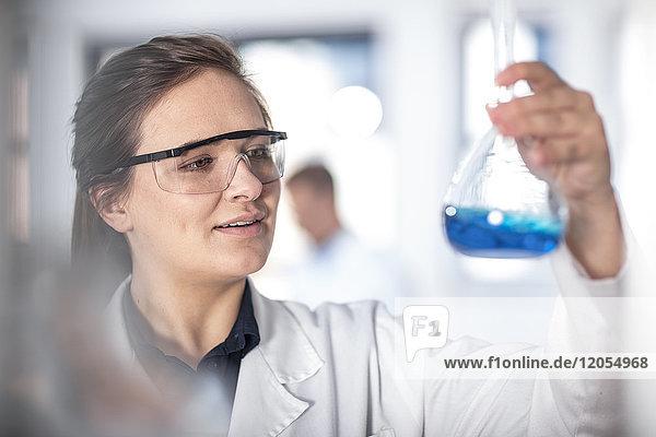 Wissenschaftler im Labor mit Blick auf die Flasche