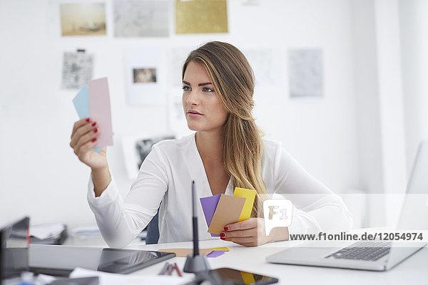 Junge Frau beim Betrachten von Notizen am Schreibtisch im Büro