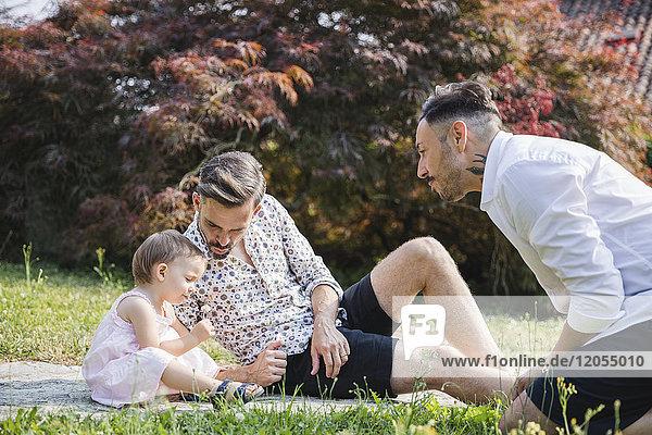 Schwules Paar  das mit seinem Kind im Garten spielt.