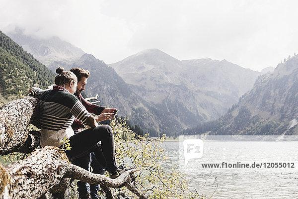 Österreich,  Tirol,  Alpen,  Paar auf Baumstamm am Bergsee mit dem Handy entspannen