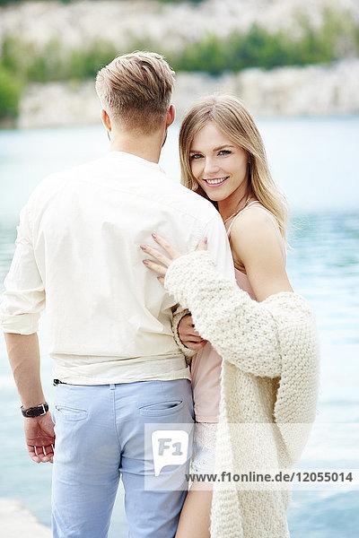 Glückliches junges Paar am Seeufer